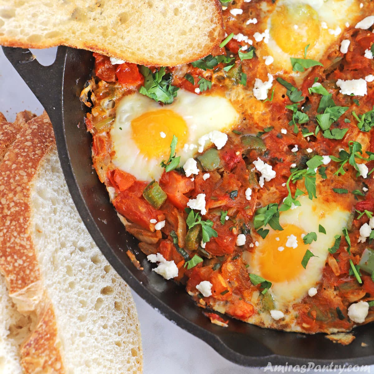 A cast iron with eggs poached in tomato sauce and feta crumbled on top.