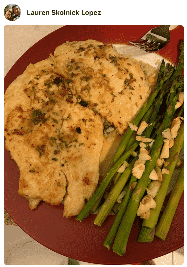 A plate of food with chicken francese and asparagus made by a fan