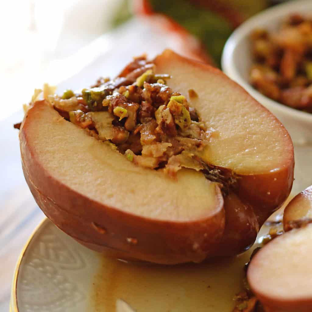stuffed apples with nuts placed on a white plate.