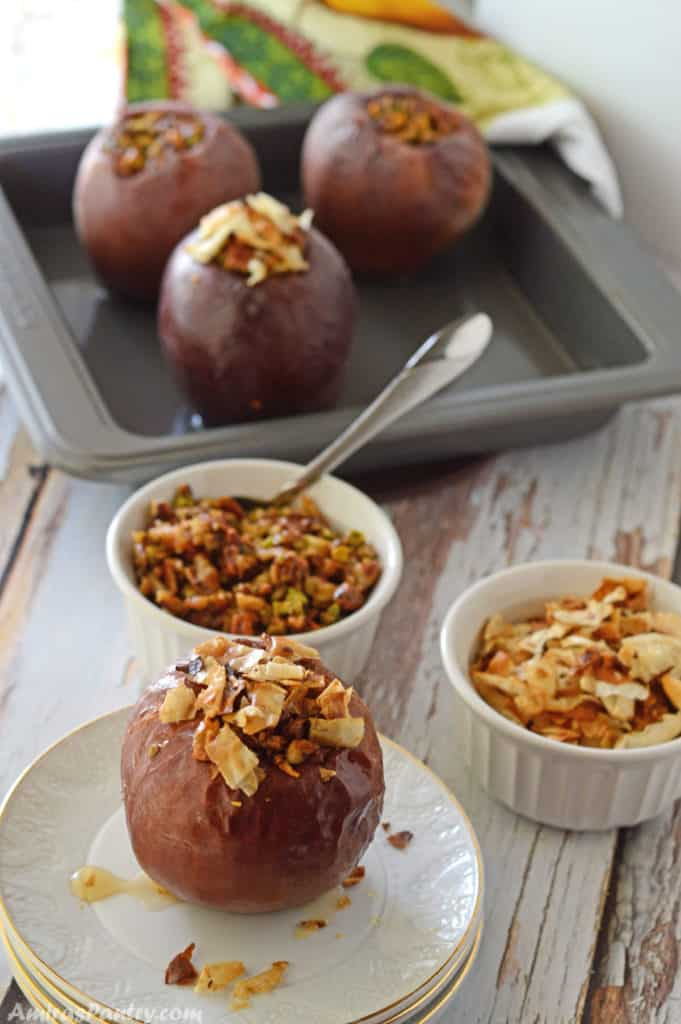 Baked apples on a wooden table with some bowls with nuts and baked phyllo dough.