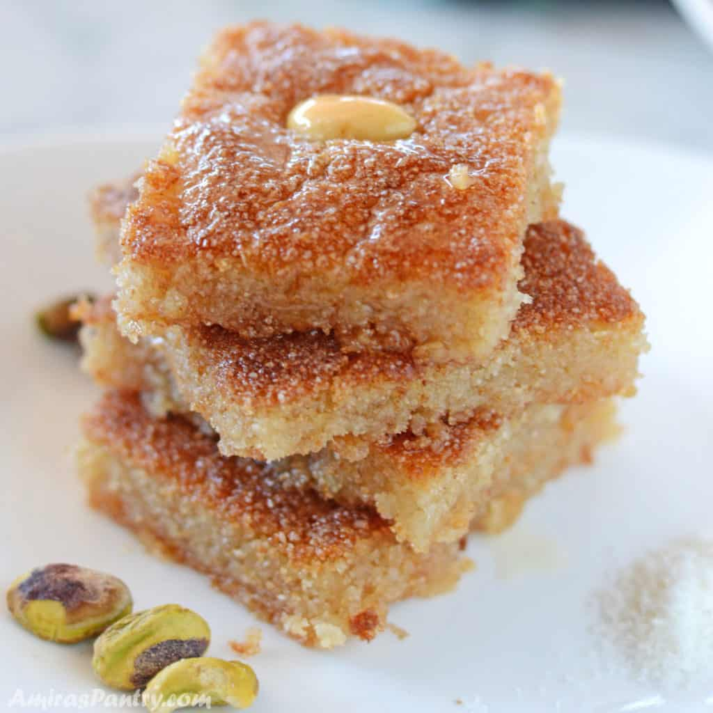 basbousa squares stacked on top of each other on a white plate