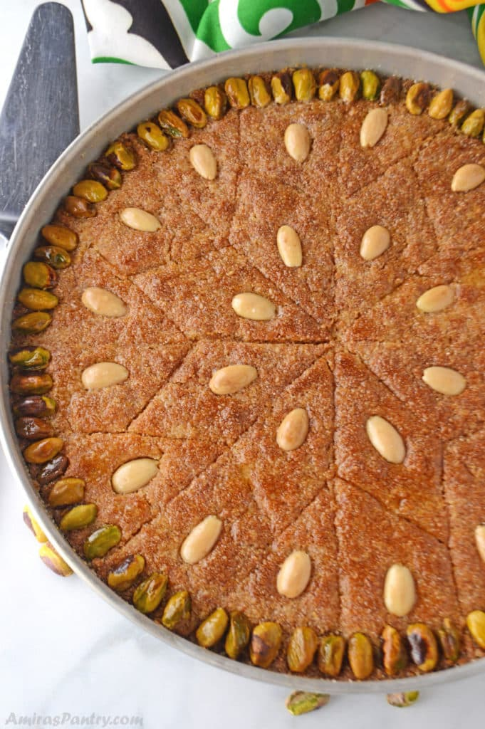 A whole tray of Egyptian basboosa garnished with pistachios and almonds.