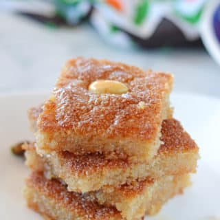 basboosa squares stacked on top of each other on a white plate