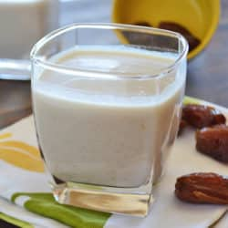 A cup of date milkshake on a white and yellow napkin on a wooden table with some dates on the side.
