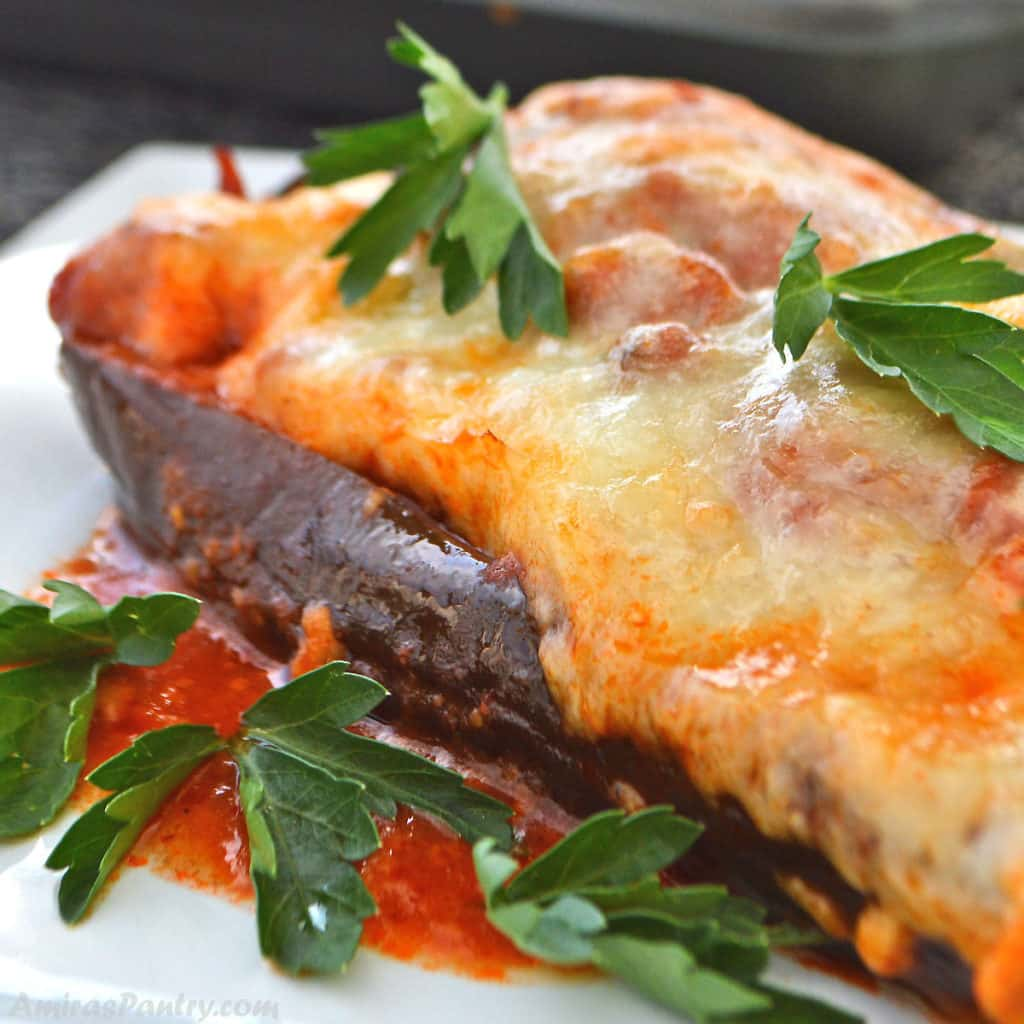 An eggplant boat topped with melted cheese and garnished with parsley.