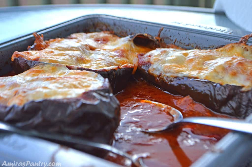 eggplant boats in a baking dish with tomato sauce.