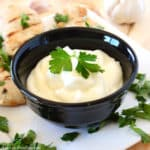 Garlic dip in a small black bowl garnished with parsley
