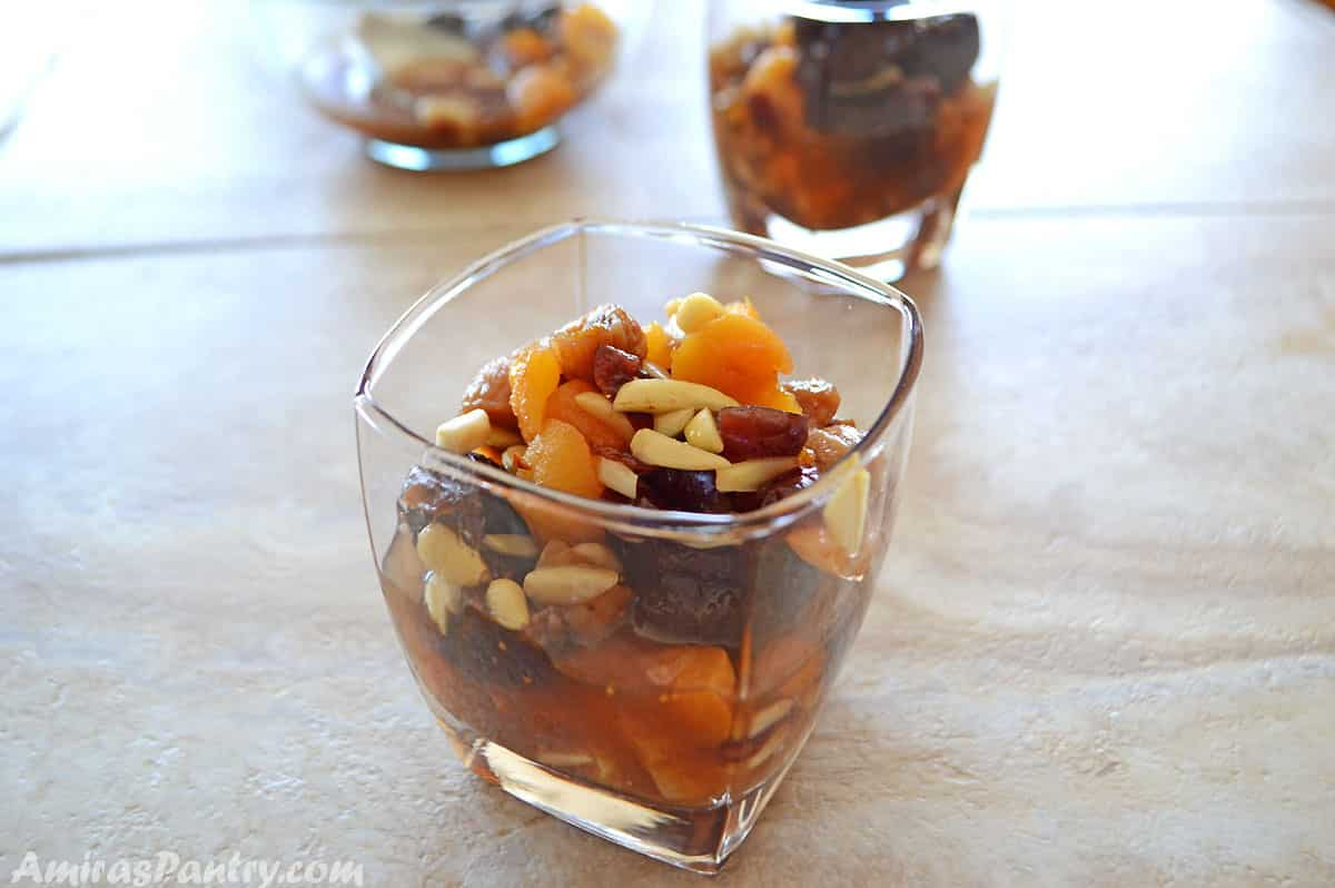 A cup of dried fruits compot placed on a tile table