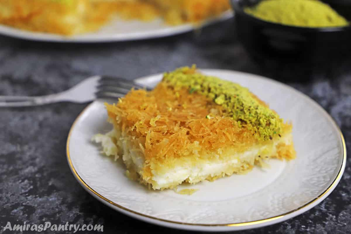 A piece of knafeh on a whote dessert plate placed on a concrete table