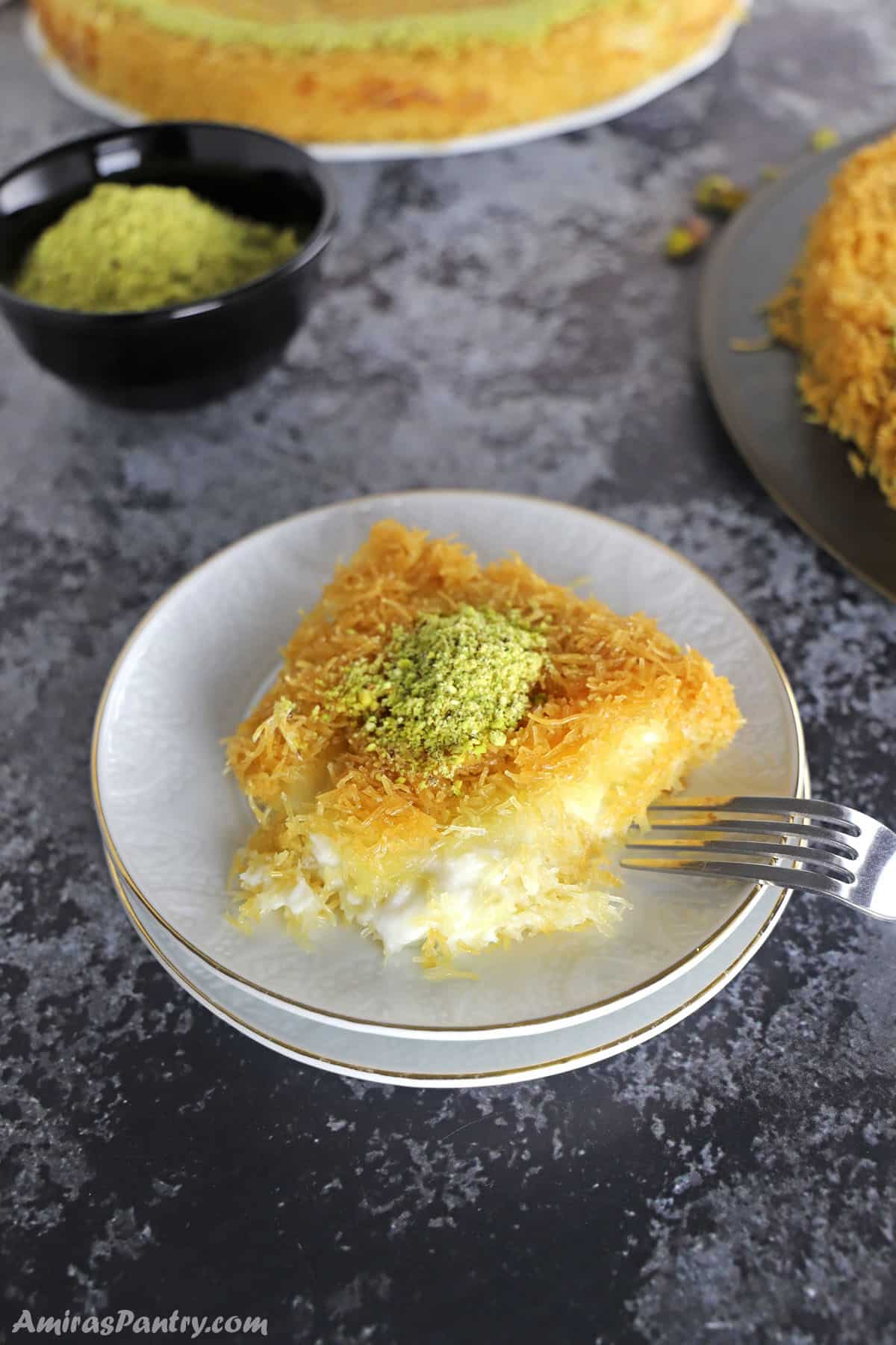 a piece of knafeh on a white dessert plate with two knafeh platters on the back