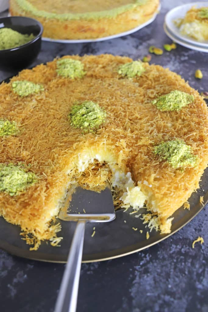 Knafeh garnished with crushed pistachios on a black metal platter.
