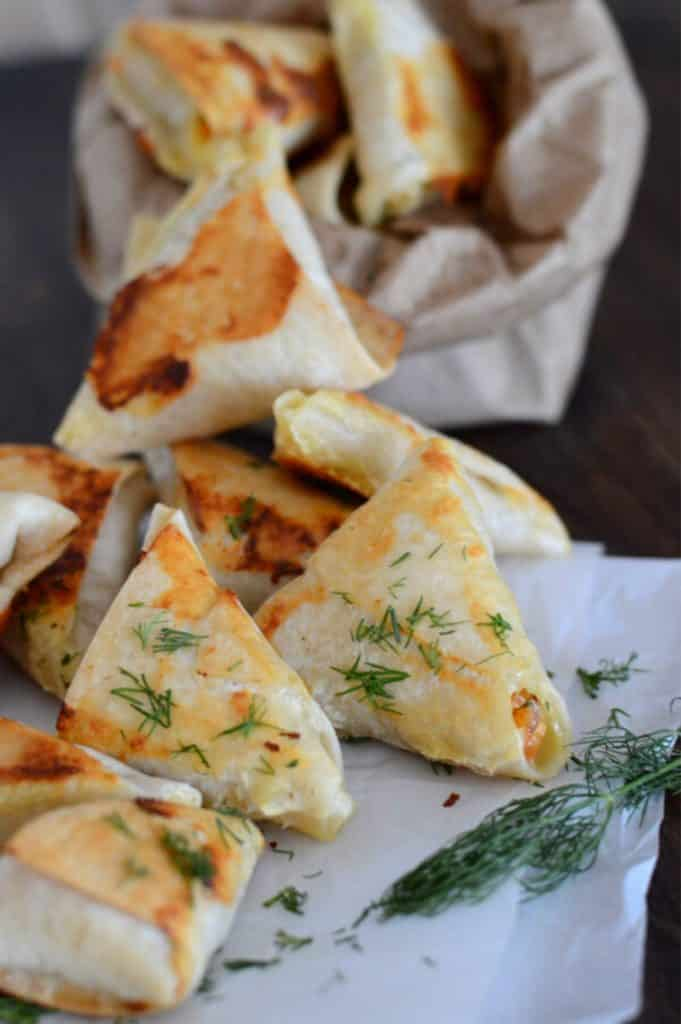 baked samosas on  placed on parchment paper on a wooden table