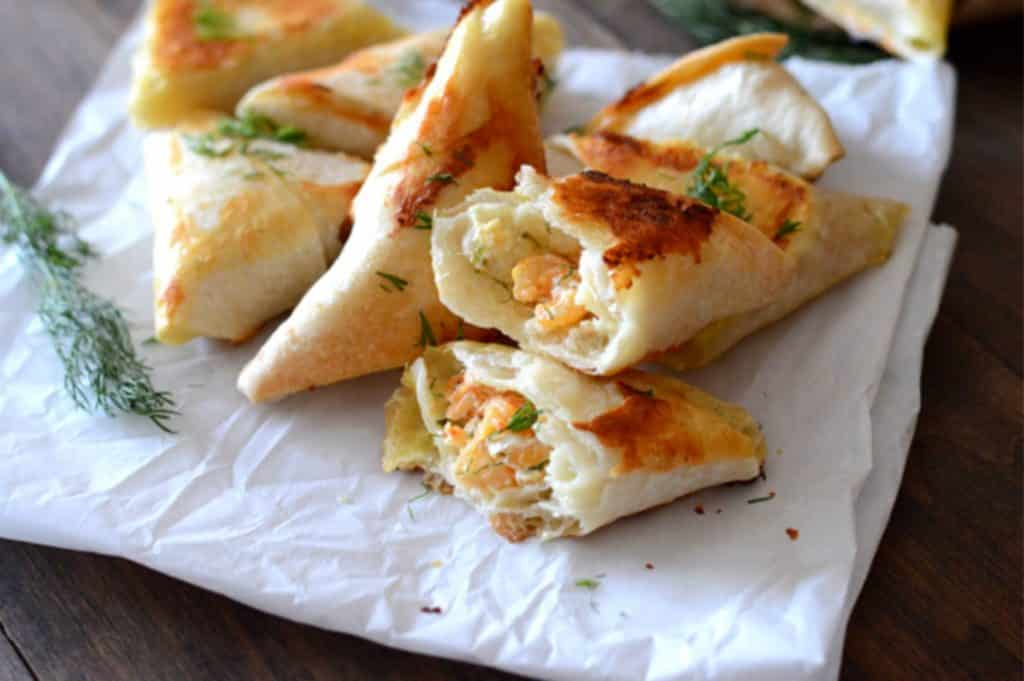 samosas on a parchment paper and cut open to show creamy dill shrimp filling