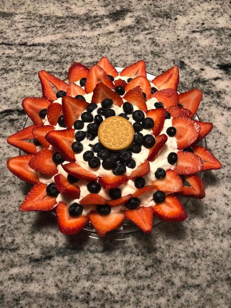 A close up of a cake with fruit on top of a table, made by a fan