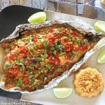 baked bass in a tin foil on a serving plate with lemon wedges and rice on the side.