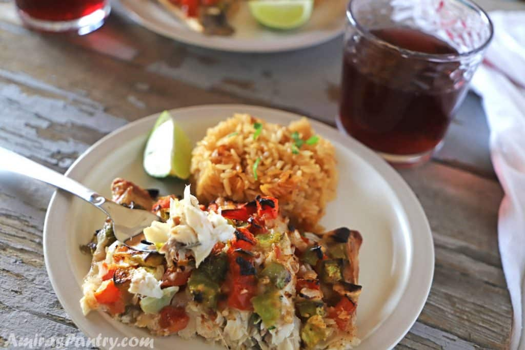 A plate with rice and a piece of baked bass with a fork and a cup of juice on the side.