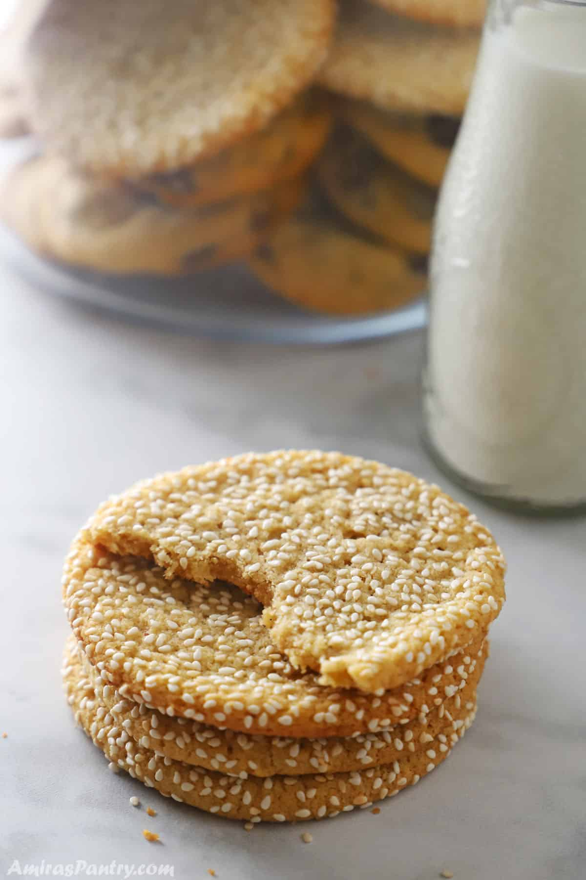 A stack of tahini cookies with a bottle of milk in the back.
