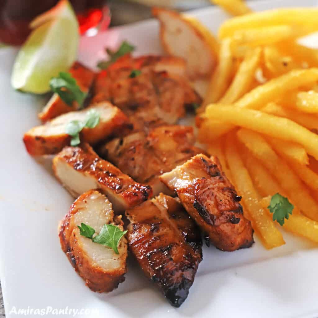 cut up grilled tenders with fries on the side.