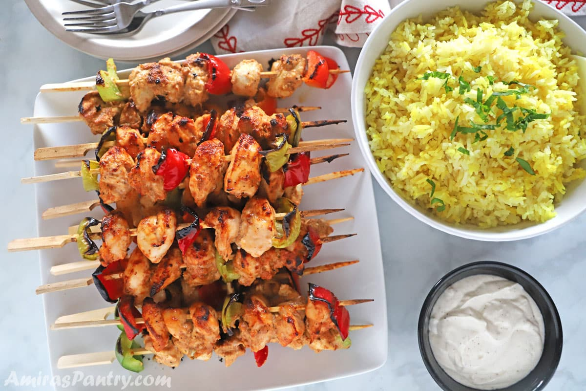 Tawook skewers placed on a white serving plate with yellow rice and toom on the side.