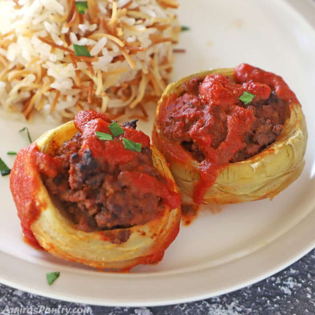 Two artichokes bottoms stuffed with ground beef and placed on a plate with Lebanese rice.