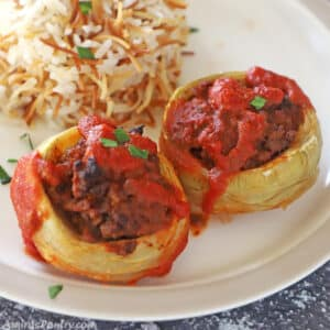 Two artichoke bottoms stuffed with ground beef and placed on a plate with Lebanese rice.