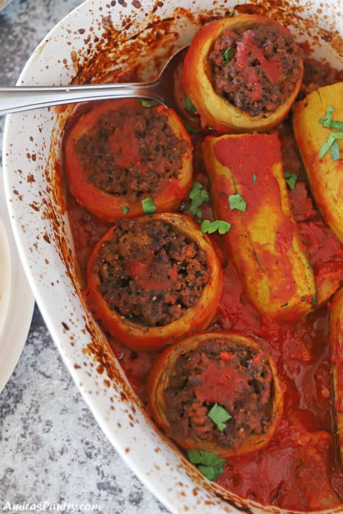 A white baking dish with stuffed artichokes and zucchini in tomato sauce.