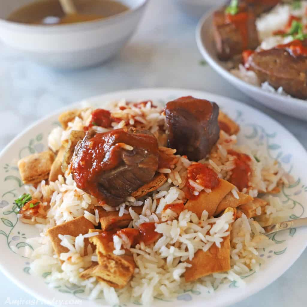 Egyptian meat fattah on a white dinner plate with bowls of sauces in the back