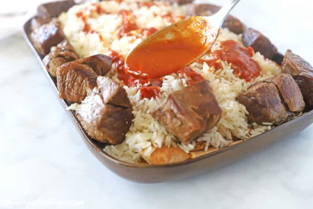 A spoon drizzling some tomato sauce over a big platter of fattah.