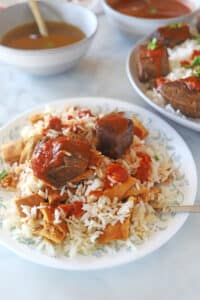 A serving of fattah on a white plate with two bowls of sauces in the back