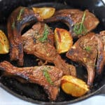 lamb chops on a cast iron skillet decorated with fresh dill and lemon wedges.