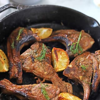 lamb chops on a cast iron skillet with lemon wedges on the side.