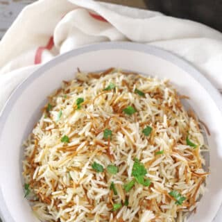 A bowl of food on a plate, with Rice