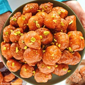 Hands holding a green plate full of loukoumades fritters decorated with crushed pistachios.