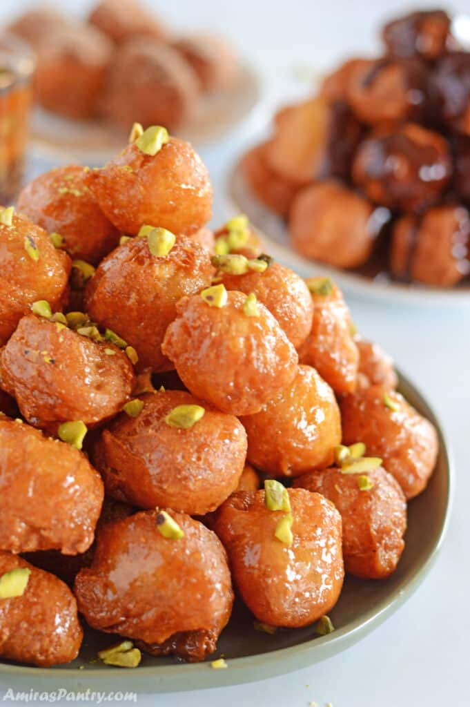 Loukoumades fritters on a green plate placed on a white table.