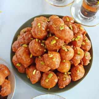 loukoumades fritters piled on a green plate with small cups of Turkish tea on the side.