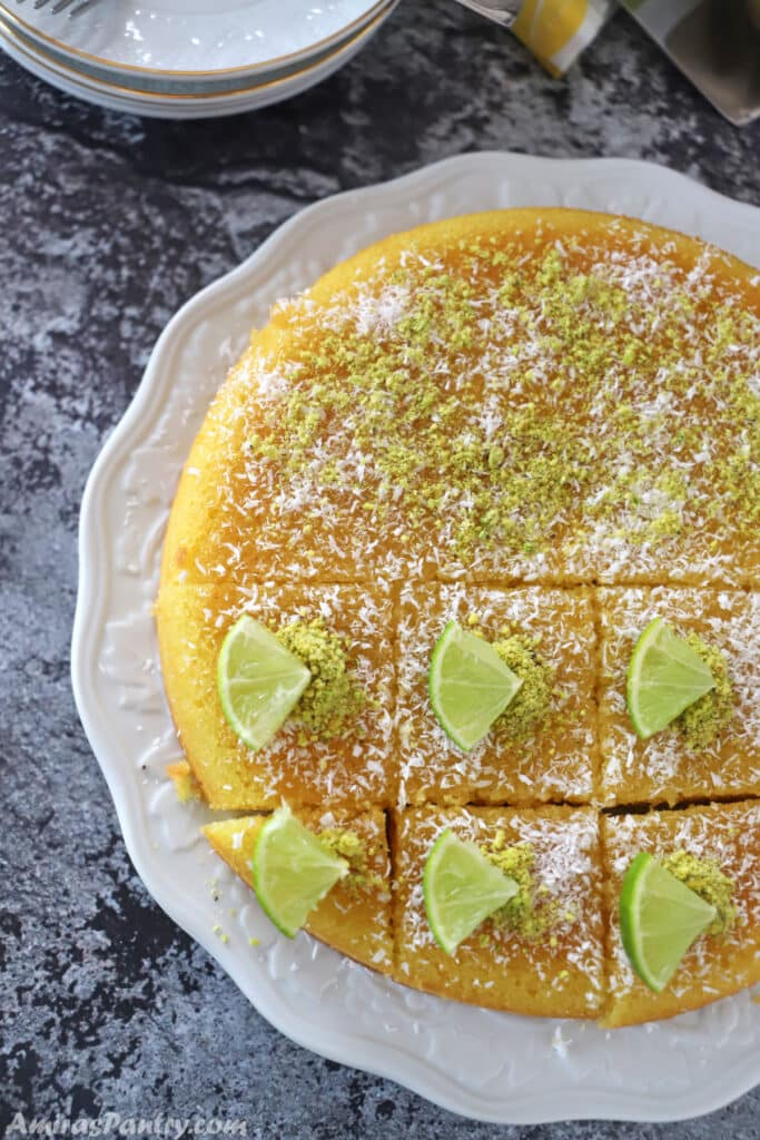Revani cake placed on a white platter and decorated with lemon pieces, coconut and crushed pistachios