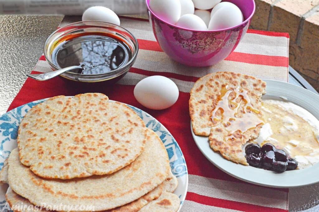 breakfast table with eggs, molasses, honey, jam and flatbread.
