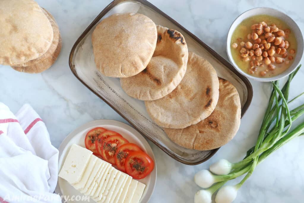 Egyptian food breakfast table with whole wheat pita, ful and white cheese.