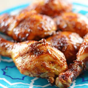 BBq drumsticks on a blue plate placed on a wooden countertop