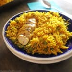 Yellow rice and chicken place on a dark blur plate with white rim