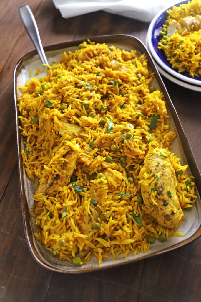 A large serving platter of yellow rice and chicken placed on a wooden table with a serving spoon on the platter.