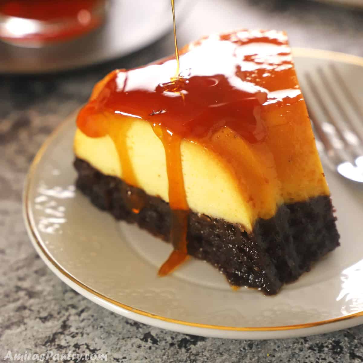 A piece of chocoflan on a white dessert plate with caramel dropping down its side.