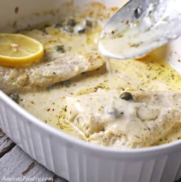 A spoon scooping some creamy sauce over the fish in a white pan.