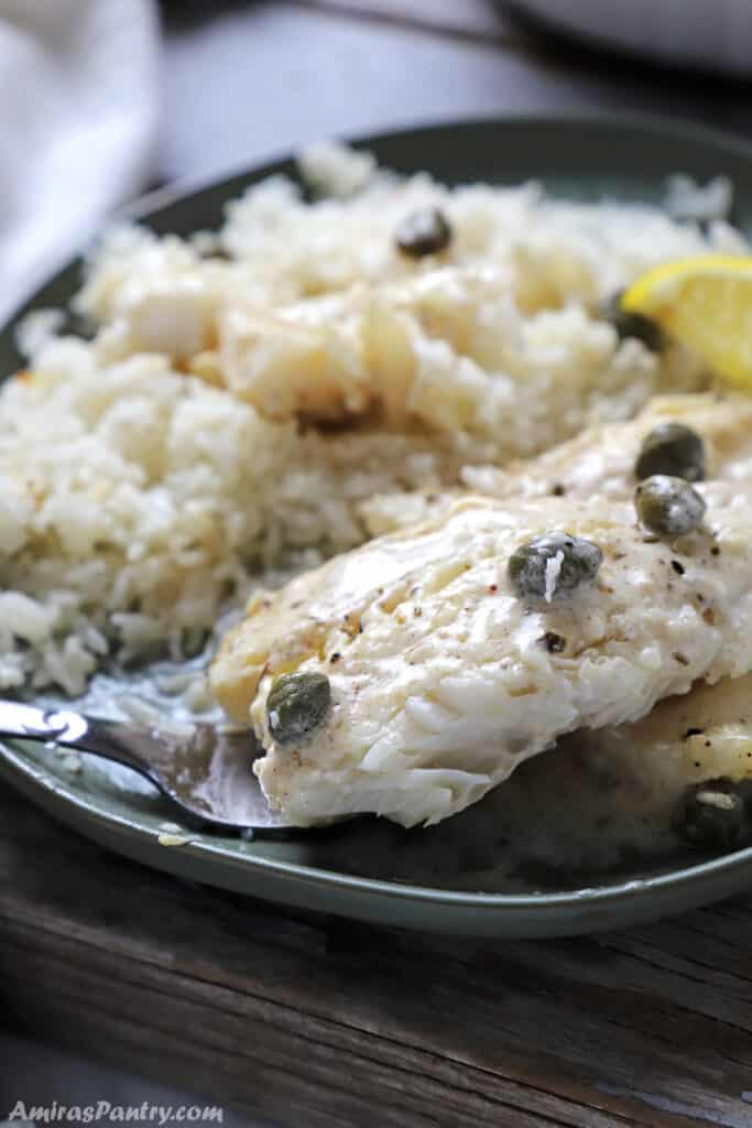 A green plate with white rice and baked cod.
