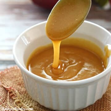 A spoon pouring some date caramel into a white bowl.