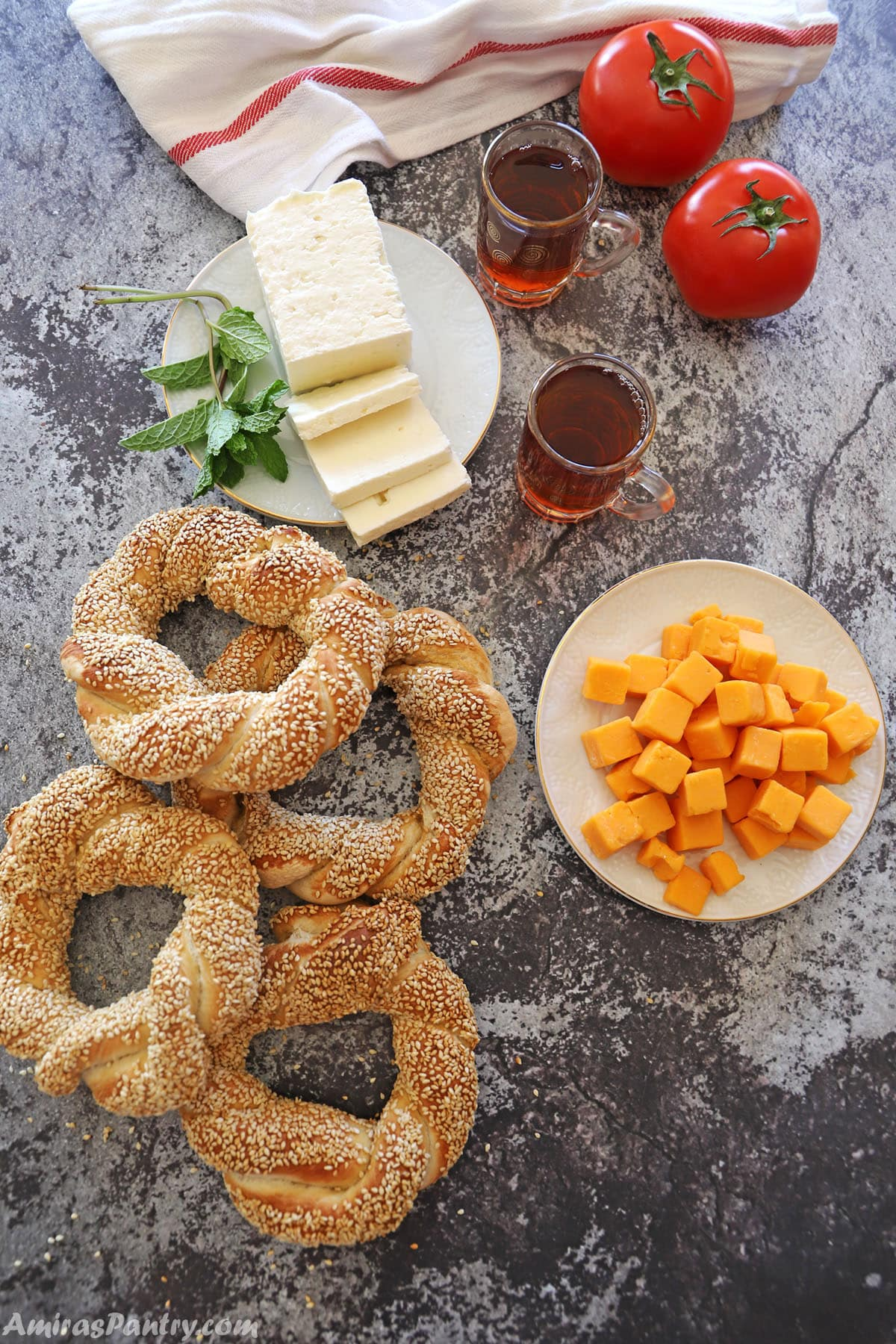 A tabletop with simit, Turkish tea cups, cheese plates and tomatoes.