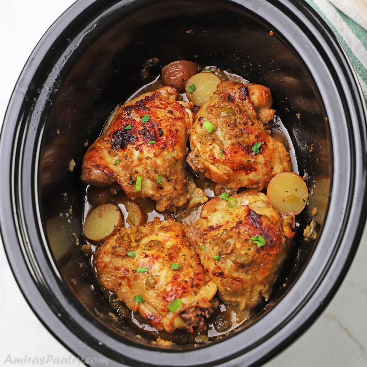 a slow cooker with chicken thighs and potatoes.