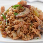 sausage stuffing in a white plate garnished with chopped parsley.