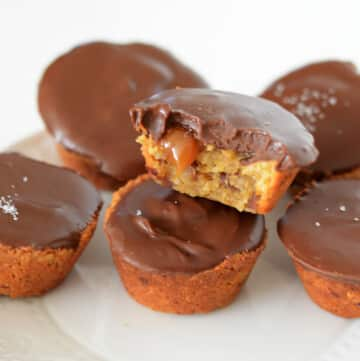 Chocolate caramel cups on top of each other on a white plate with a bite take from one showing some caramel dripping.