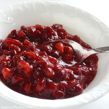 Cranberry sauce in a white bowl with a spoon in it.